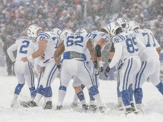 Indianapolis Colts players work to remove snow from the path of kicker Adam Vinatieri (4) late in the game against the Buffalo Bills in the fourth quarter at New Era Field in Orchard Park, N.Y., on Sunday, Dec. 10, 2017.