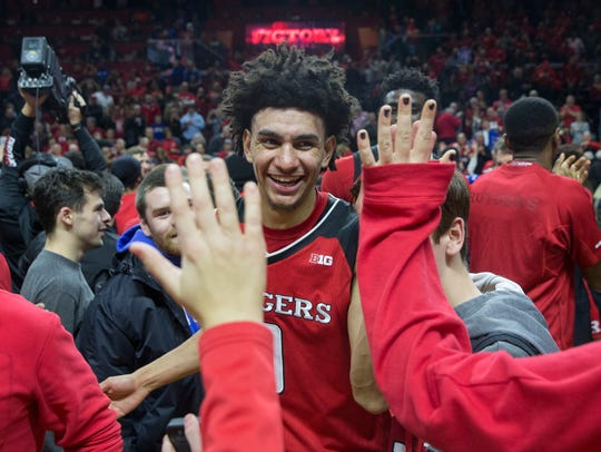 Rutgers guard Geo Baker celebrates with fans.