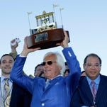 Triple Crown winner American Pharoah's trainer Bob Baffert, center, owner Ahmed Zayat, right, and his son Justin Zayat, left, celebrate with the winner's trophy after American Pharoah won the Haskell Invitational horse race at Monmouth Park in Oceanport, N.J., Sunday, Aug. 2, 2015. Keen Ice  was second. (AP Photo/Mel Evans)