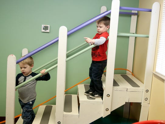 Marcus Harder, 4, goes down the stairs with his twin brother, Lucas, at Kitsap Children's Therapy in Poulsbo. The boys attend developmental preschool together and have been separated eight days their entire life.
