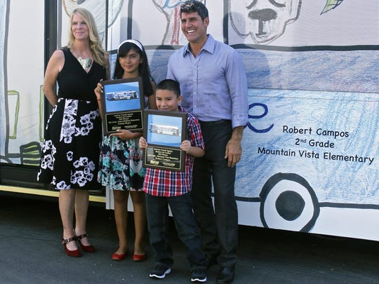 Fifth grader Lianna Reyes and second grader Robert Campos pose for a photograph with Lauren Skiver, SunLine Transit Agency's CEO, and Vincent Battaglia, Renova Solar's CEO, Wednesday, at the Renova Solar office in Palm Desert. The students' artwork will be showcased on SunLine Transit Agency buses throughout the valley for the next year as part of SunLine's annual student art contest.