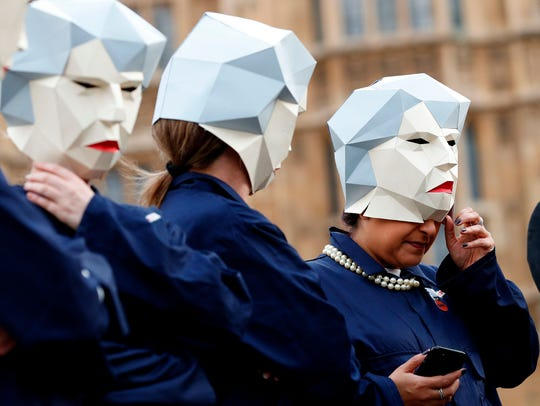 A demostrators dressed Britain's Prime Minister Theresa