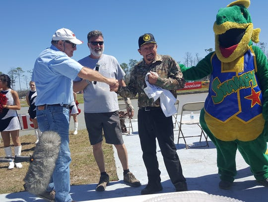 Leonard Chesser (right) shakes hands with Swamp Buggy