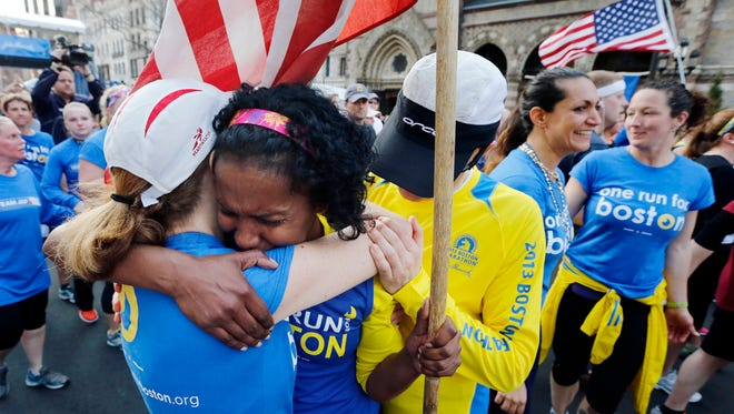 Rosa Evora, center, hugs a fellow participant in a cross country relay that began in March in California and ended at the Boston Marathon finish line in Boston, Sunday, April 13, 2014.