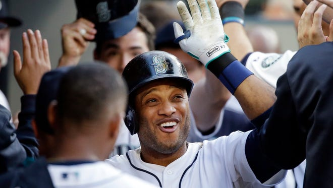 Seattle Mariners' Robinson Cano is congratulated by teammates after his two-run home run against the Cleveland Indians in the third inning of a baseball game Saturday, May 30, 2015, in Seattle.