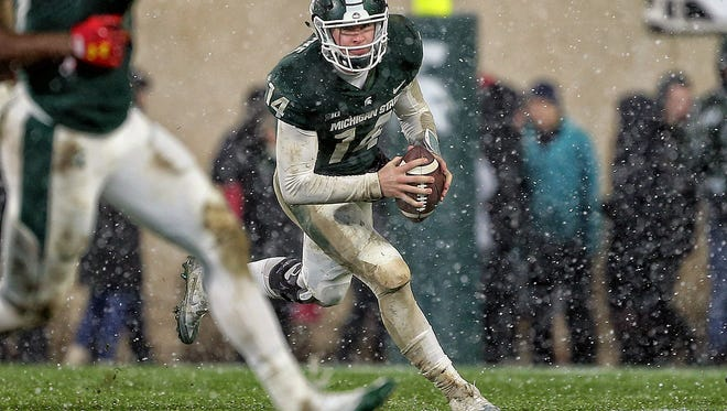 Michigan State quarterback Brian Lewerke (14) scrambles out of the pocket during the first half on Saturday, Nov. 18, 2017, at Spartan Stadium.