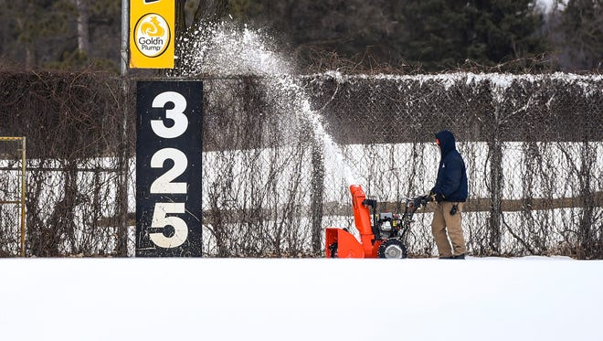 Groundskeeper Tim Kuhl blows snow off the warning track in the outfield Tuesday, April 10, around Joe Faber Field at the Municipal Athletic Complex.