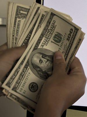 A man counts US Dollar bills at an exchange bureau on January 24, 2014.