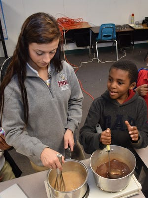 Pineville High School junior Jamie Coutee (left) stirs apple cider syrup while Julius Patrick Elementary student De'Shaun Milton stirs hot chocolate during a culinary arts elective at JPE Tuesday.