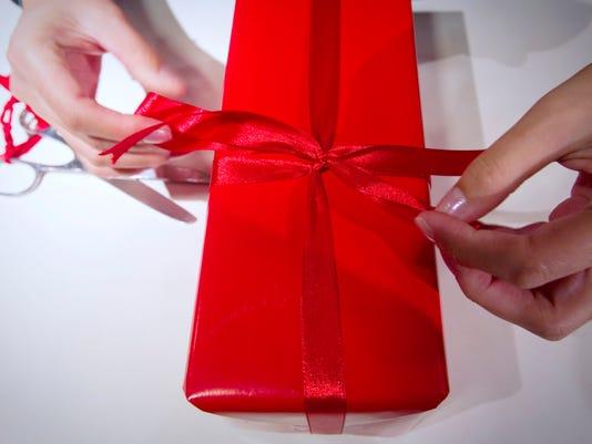 A seller wraps a gift in a Parisian depa