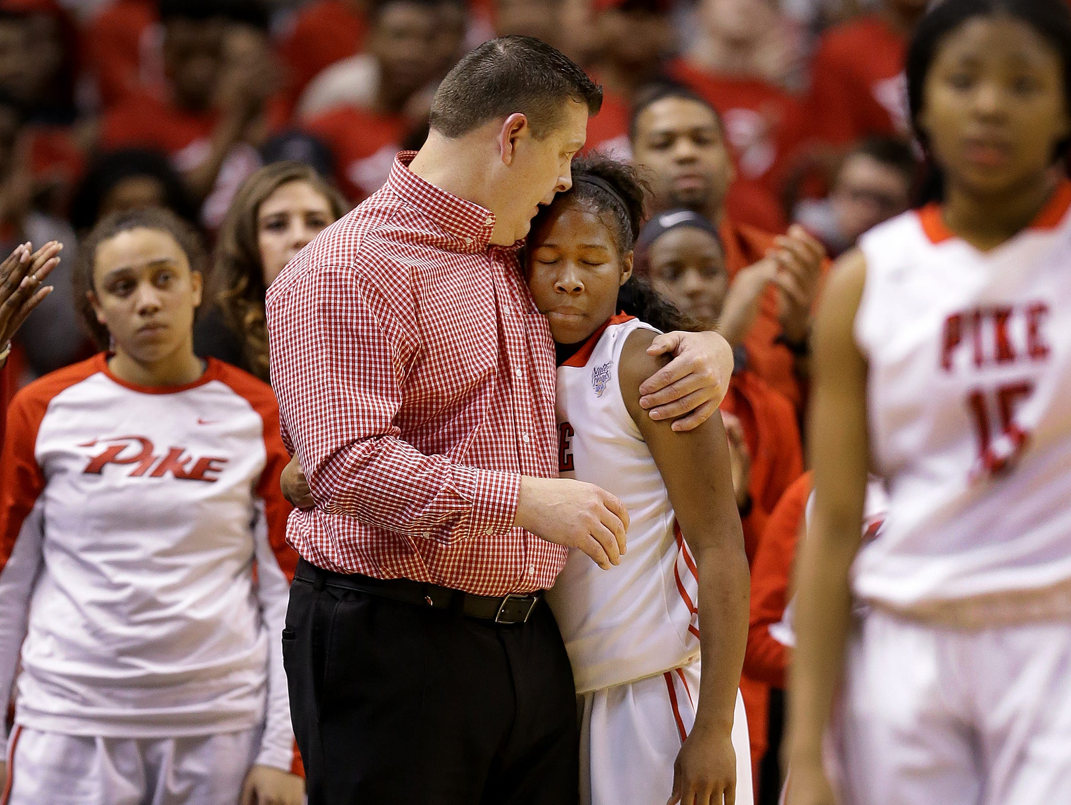 Pike Red Devils head coach Robert Anglea comforts Jada Robertson (3) after she fouled out late in the second half of their IHSAA 4A Girls Basketball State Finals game Saturday, February 25, 2017, evening at Bankers Life Fieldhouse. The Homestead Spartans defeated the Pike Red Devils 61-54.