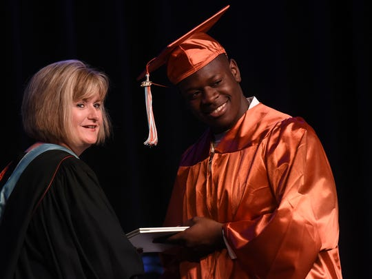 Northwood principal Darlene Simons distributes a diploma during the schools' commencement ceremony last month. The school is expected to see a spike in enrollment over the next few years.
