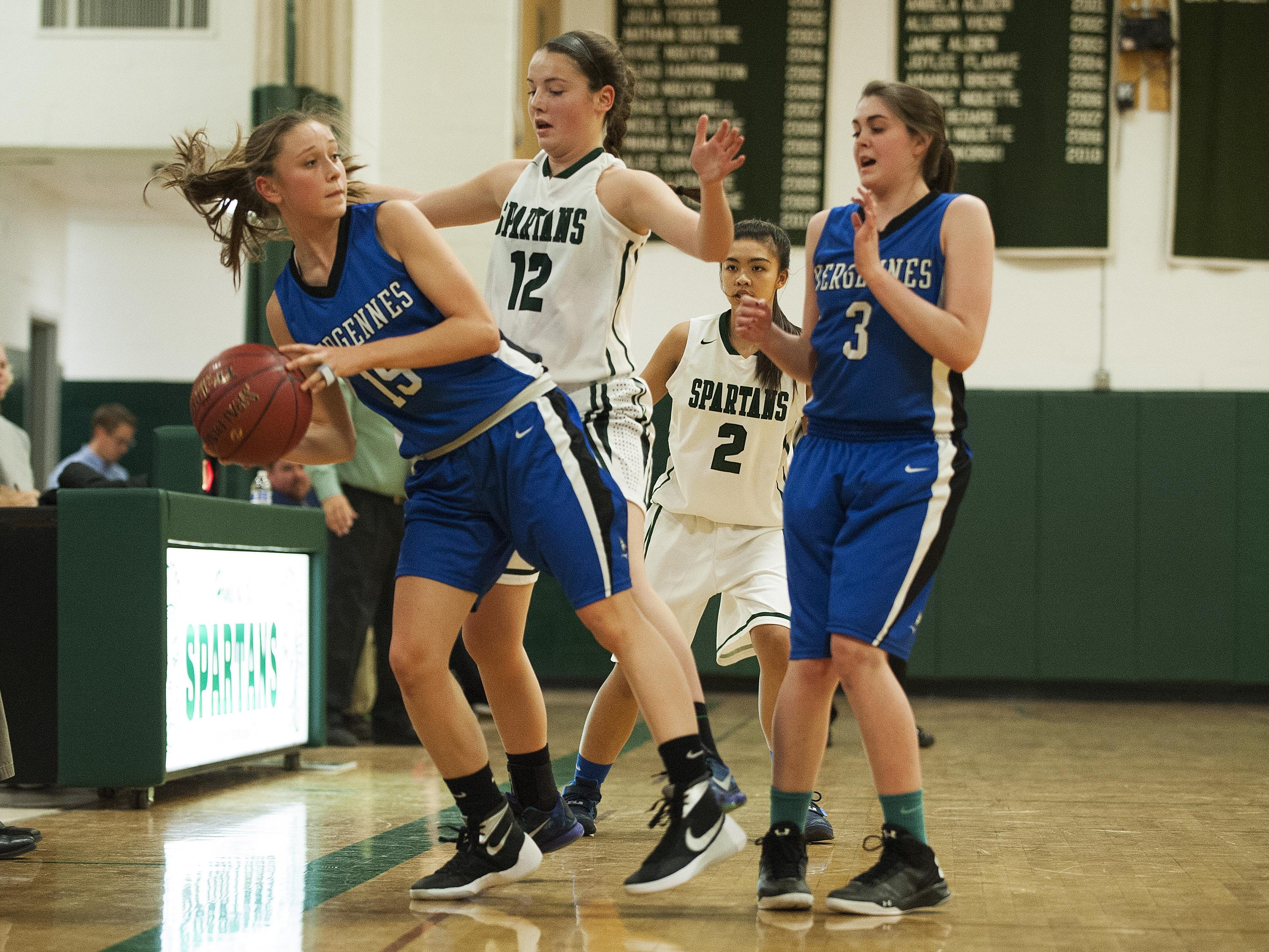 Vergennes' Caroline Johnston, left, tries to save the ball from going out of bounds while being guarded by Winooski's Lydia Nattress (12) during the girls basketball game at Winooski High School on Wednesday night