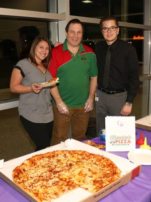 Westland Wild Walkers Relay for Life team members Aubrey Berman (left) and Devon Adams flank Lou Toarmina of Toarmina's Pizza at the event kickoff.