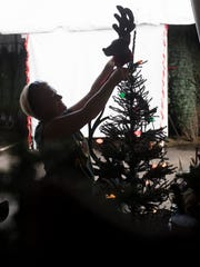 Janice Clark, an employee of Heath's Christmas Trees  prepares a display on Tuesday 11/28/2017.