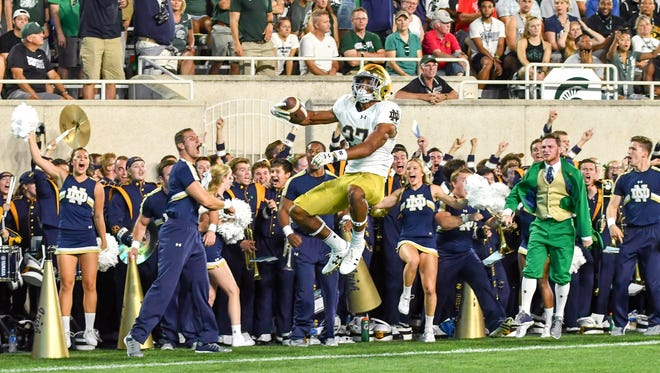 Sep 23, 2017; East Lansing, MI, USA; Notre Dame Fighting Irish cornerback Julian Love (27) jumps into the end zone after scoring a touchdown on an interception return in the first quarter against the Michigan State Spartans at Spartan Stadium. Mandatory Credit: Matt Cashore-USA TODAY Sports