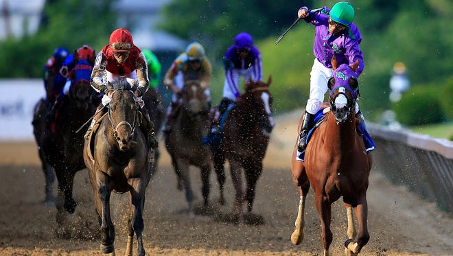 California Chrome, ridden by Victor Espinoza, crosses the finish line to win the 139th running of the Preakness Stakes at Pimlico Race Course in front of Ride On Curlin.