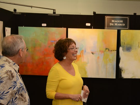 Maggie De Marco, right, discusses her abstract paintings with patrons.