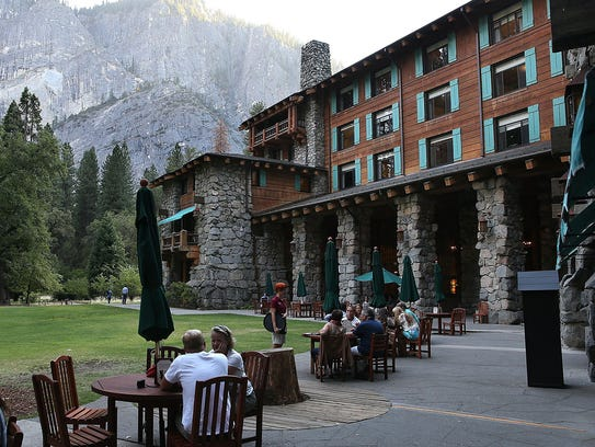 Park visitors sit outside of the Ahwahnee Hotel on