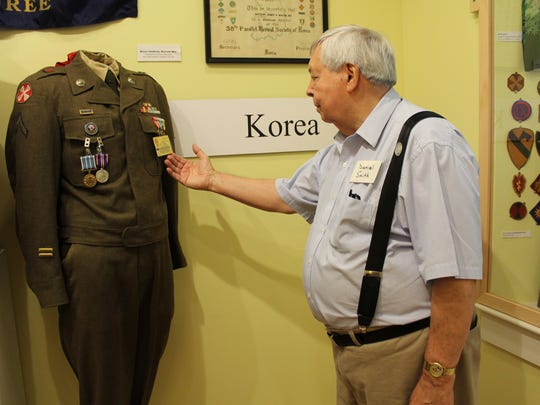 Daniel Smith, a volunteer at the museum and Korean War vet, looks at a Korean War uniform like the one he wore.