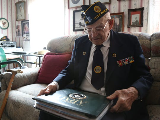 Ralph Osterhoudt brings out his scrap book at his home in Hyde Park on May 18, 2018. Ralph served in WWII.
