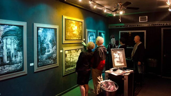 Art lovers check out the surrealistic art and concert photography at The Reverie & Rock Art Gallery during the June Art Walk in downtown Fort Myers.