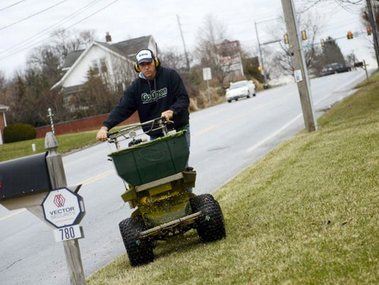 Phil Holloway, owner of Go Green, spreads fertilizer on a client's lawn in Red Lion last year. Kate Penn  Äî Daily Record/Sunday News