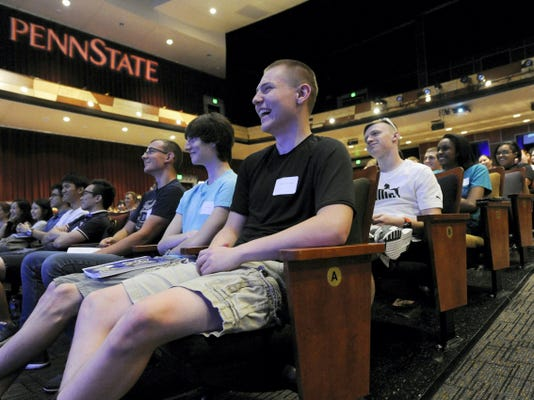 Jedidiah Lieberknecht, center, of Dover, reacts to the motivational speech of Andy Stoll during orientation for incoming freshmen on the college campus of Penn State York on Friday, August 21, 2015.