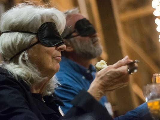 Suzanne Gates and husband Bill Goldberg of Thomasville eat dinner blindfolded during the ForSight Vision event Dining in the Dark Thursday at Wyndridge Farm. Watch a video from the event at yorkdispatch.com.