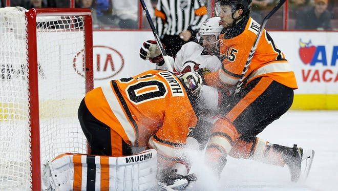 Michael Del Zotto left the game after this collision with goalie Michal Neuvirth and New Jersey Devil Kyle Palmieri.