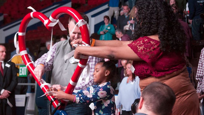 Community members tie ribbons on the infinity hear that is the logo for ForeverStrong at a memorial service for the victims of the 2016 Kalamazoo, Mich., mass shooting at the Wings Event Center in Kalamazoo on Monday, Feb. 20, 2017.