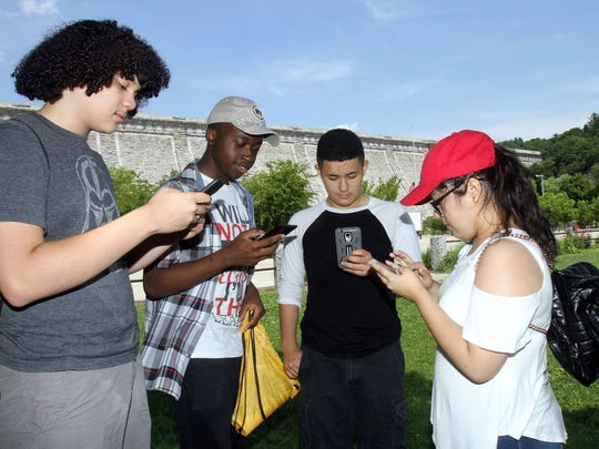 From left, Colin Regan, 16, of Hartsdale, Tyler Venzen, 16, of White Plains, Andres Espinoza, 17, of Greenburgh, and Aileen Bravo, 15, of Greenburgh, play the  Pokemon game at the Kensico Dam Plaza in Valhalla July 12, 2016.