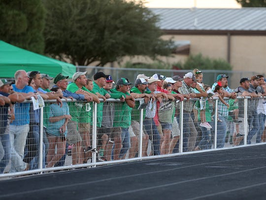Wall fans lineup against the fence to watch their team take on the Mason Punchers during the Friday, Aug. 31, 2018, football game in Wall.