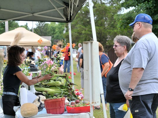 People buy produce at the Kronenwetter farmers market.