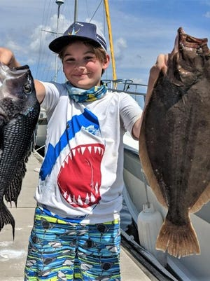 """""""This is the biggest fluke I ever caught,"""" says Mason Coffey, 11, as he displays a 22-inch summer flounder and 21-inch black sea bass he caught off Newport fishing with his father, Travis."""