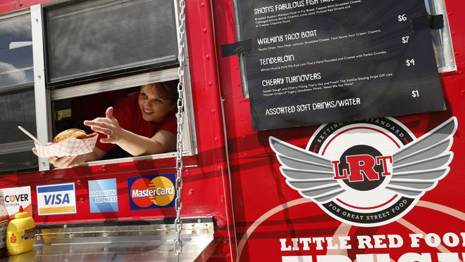 Julie Bruellman hands a customer his order Tuesday, July 7, 2015, from the Little Red Food Truck parked along 15th street by the sculpture park in downtown Des Moines.