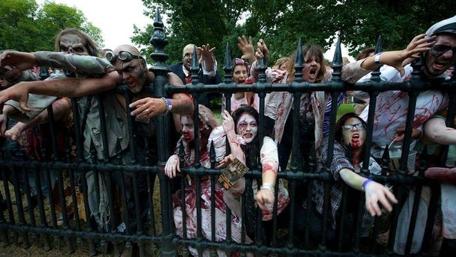Zombie-adorned participants reach through the fence during a past event in Newburgh.