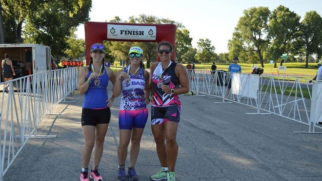 """Emily """"Martz"""" Foerschler, Holly Reed Osborn and Jennifer Woods show off their medals after the race."""