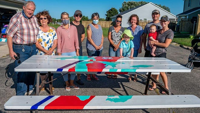 Dennis Despain, Rosalie Despain, Kira Boyd, Jeff Boyd, Kathy Johnson, Billy Mullinger, Magda Pastwikowski, Caloeb Gandy and Leah Gandy unveil the Coast Guard Table which will soon be able to be seen at Gordon Turner Park.  Photo by Tony Johnson