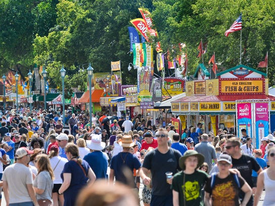 Crowds of fair-goers walk along Ligett Street on the Minnesota State Fairgrounds during the 2015 Minnesota State Fair.