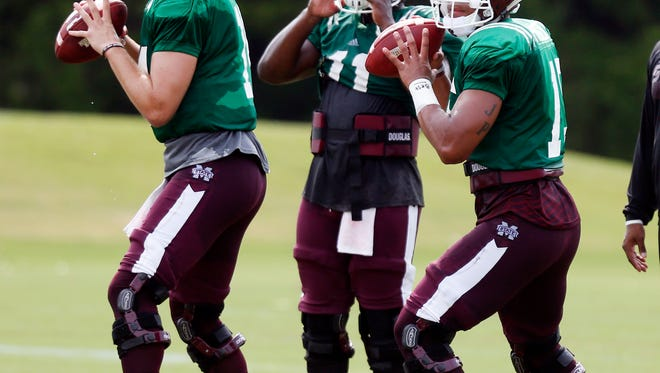 Mississippi State quarterbacks Dak Prescott, right, and Nick Fitzgerald, left, set up to pass as quarterback Damian Williams (11) readies during drills at an NCAA college football practice in Starkville, Miss., Friday, Aug. 7, 2015. (AP Photo/Rogelio V. Solis)