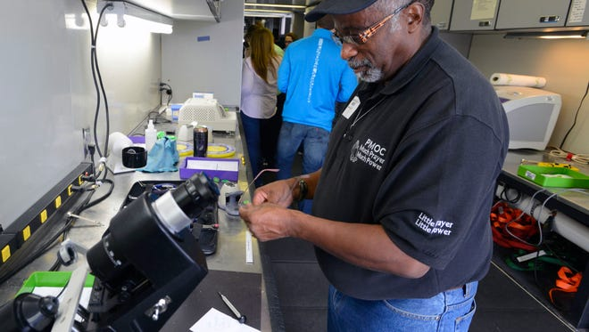 Optometrist Edward Mitchell Jr. makes a new pair of glasses at a previous Remote Area Medical clinic, where patients received free medical, dental and vision services. Volunteers are being recruited for an upcoming clinic Dec. 2-3 at Pensacola High School.
