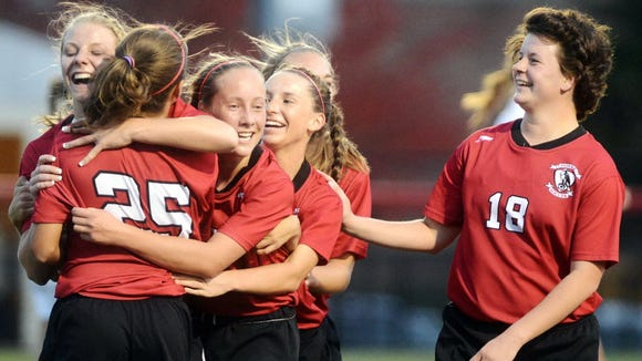 Dover's Maxine Herman, left rear, is congratulated by teammates Brooke Firestone (25), and from right Emily Firestone, Maddy Miller, and Kayla Miller after scoring her second goal of the night against Dallastown during the YAIAA soccer tournament title game last year at Susquehannock High School. (DAILY RECORD/SUNDAY NEWS -- KATE PENN)