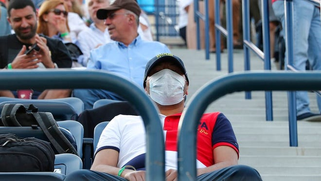 FILE - In this Friday, Feb. 28, 2020, file photo, a tennis fan wearing a facemask waits for the start of the semifinal matches of the Dubai Duty Free Tennis Championship in Dubai, United Arab Emirates. The ATP called off all men's professional tennis tournaments for six weeks because of the COVID-19 pandemic, but a WTA spokeswoman told The Associated Press on Thursday, March 12, 2020, that the women's tour was not immediately prepared to do the same.