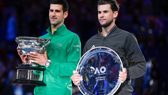 Serbia's Novak Djokovic, left, holds the Norman Brookes Challenge Cup after defeating Austria's Dominic Thiem in the final of the Australian Open tennis championship in Melbourne, Australia, Monday, Feb. 3, 2020.