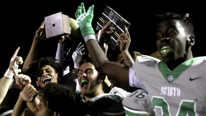 Dublin Scioto players celebrate with the Hard Road and Thursday Night Lights trophies after defeating host Worthington Kilbourne 21-13 in the Battle of Hard Road on Sept. 3.