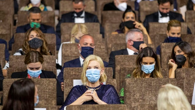 FILE - Jury President Cate Blanchett, center, is seated at the start of the opening ceremony of the 77th edition of the Venice Film Festival at the Venice Lido, Italy, on Sept. 2, 2020. This year, three of the four major fall film festivals, including Venice, are going forward despite the pandemic. Those in Venice acknowledge it hasn't been anywhere near the same. Masked moviegoers in set-apart seats. A barrier walls off the red carpet to discourage crowds of onlookers. Greetings are kiss-less. A little bit of the romance of movies has gone out.