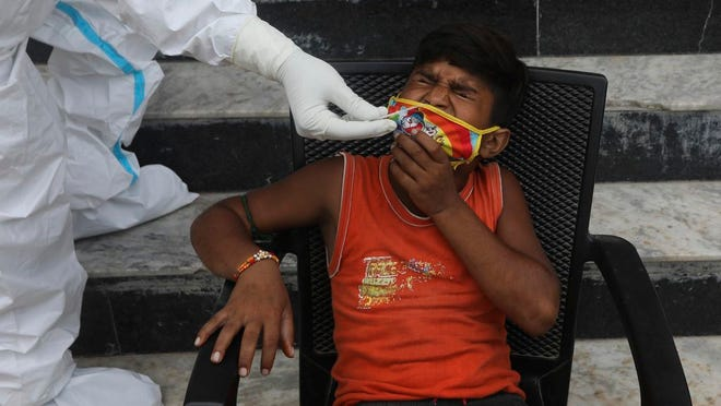 A child grimaces as a health worker takes a nasal swab sample for COVID- 19 testing through rapid antigen methodology, in New Delhi, India , Friday, Aug. 7, 2020. As India hit another grim milestone in the coronavirus pandemic on Friday, crossing 2 million cases and more than 41,000 deaths, community health volunteers went on strike complaining they were ill-equipped to respond to the wave of infection in rural areas.