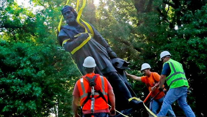 A statue of Christopher Columbus, erected in Tower Grove Park in St. Louis 140 years ago, is taken down Tuesday, June 16, 2020, at the direction of the park's Board of Commissioners. Such statues have come down in other U.S. cities after being viewed by some as symbols of exploitation. It will be cleaned and put in storage, with its future undecided.
