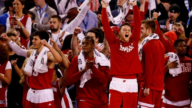 Wisconsin Badgers players celebrate after defeating Kentucky in Saturday night's NCAA tournament semifinal at Lucas Oil Stadium in Indianapolis.